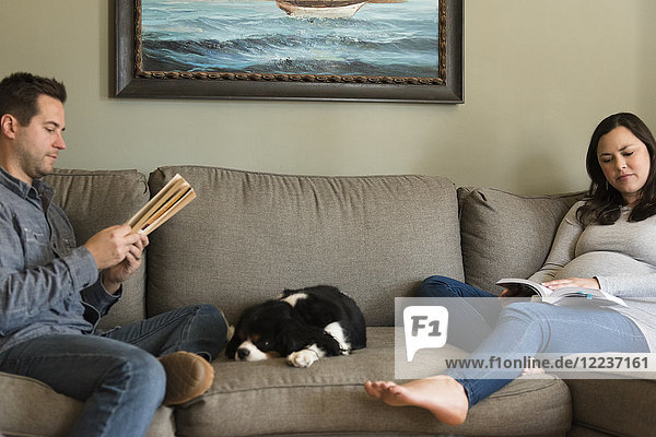 Mid adult couple relaxing on sofa with puppy in middle