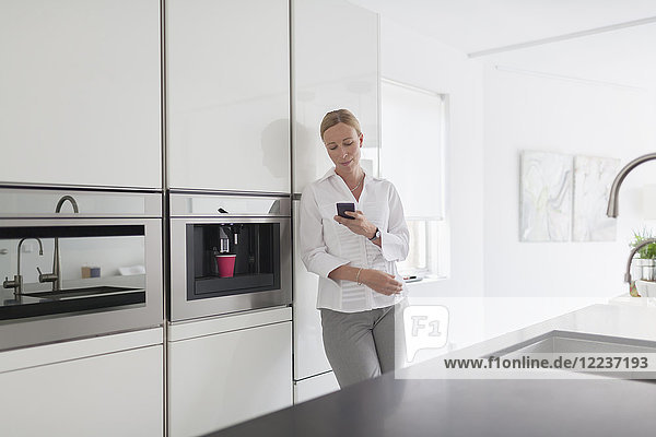 Woman using phone in kitchen