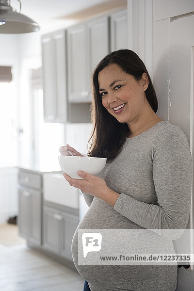 Pregnant woman standing in kitchen  holding bowl