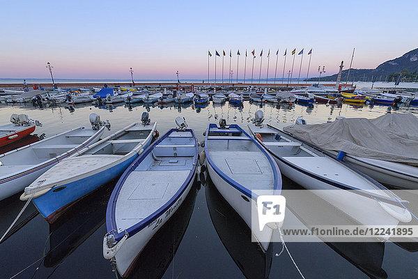 Harbor marina with rows of docked fishing boats Lake Garda (Lago di Garda) at dawn in Garda in Veneto  Italy