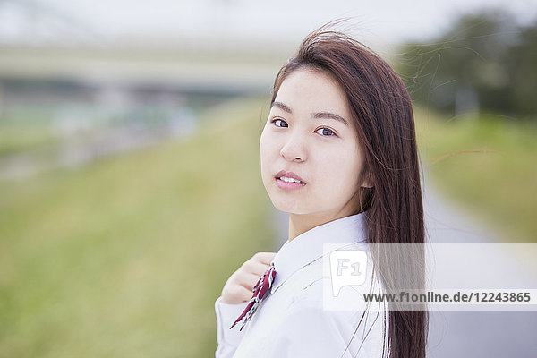Cute Japanese high school student in a city park