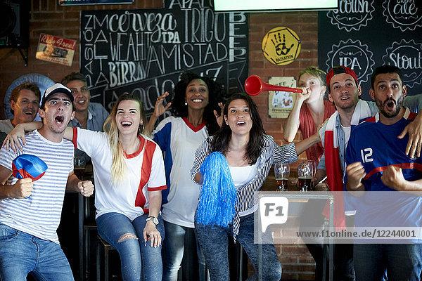 Französische Fußballfans schauen Fußballspiel im Fernsehen in der Kneipe an