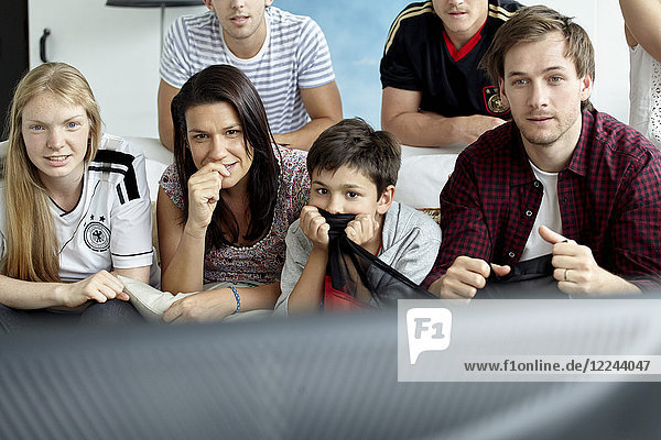 German football fans watching match on TV at home