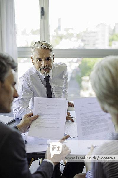 Paar Lesedokument beim Treffen mit dem Geschäftsmann