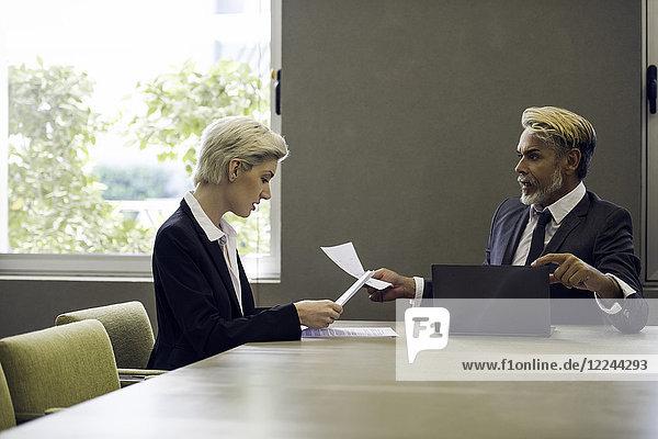 Frau und Mann im Büro lesen Dokument