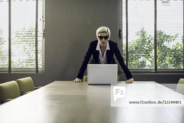 Frau im Anzug lehnt sich an den Tisch und schaut in die Kamera.