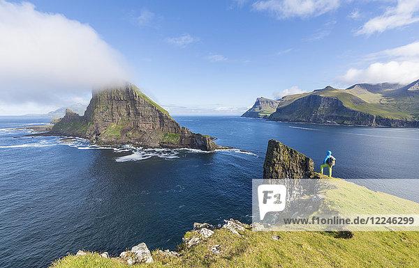 Man looks towards the sea stacks of Drangarnir and Tindholmur islet  Vagar Island  Faroe Islands  Denmark  Europe