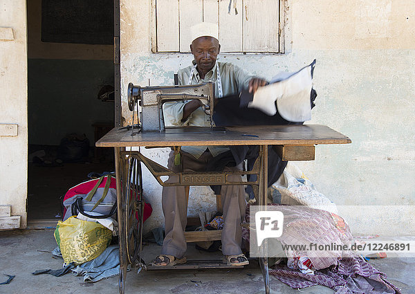 A local man making clothing with an old Singer Sewing Machine in Pangani  Tanzania  East Africa  Africa