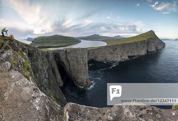Panoramic of photographer on cliffs above lake Sorvagsvatn  Vagar Island  Faroe Islands  Denmark  Europe