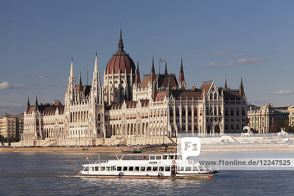 Excursion boat on the Danube River  Parliament Building at sunset  UNESCO World Heritage Site  Budapest  Hungary  Europe