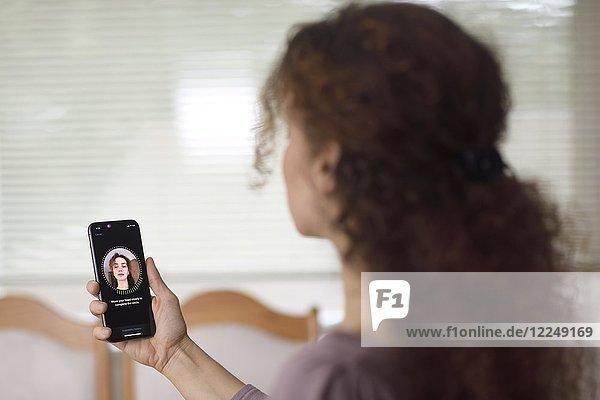 Frau mit Apple iPhone X Smartphone in der Hand mit Face ID  biometrische Authentifizierung App