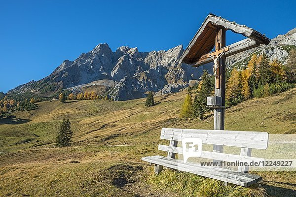 Wooden cross and bench  behind it the Eisenspitze  Dawin-Alpe  Strengen am Arlberg  Tyrol  Austria  Europe