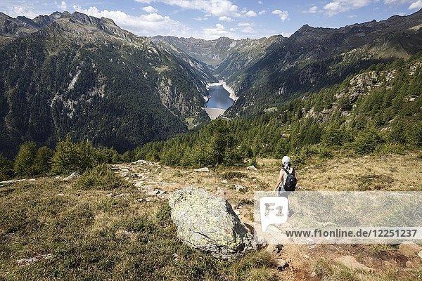 Wanderin auf dem Wanderweg von der Alpe Corte del Sasso zur Alpe Corte di Mezzo  hinten Stausee Sambuco  Lago di Sambuco  Fusio  Lavizzara  Kanton Tessin  Schweiz  Europa