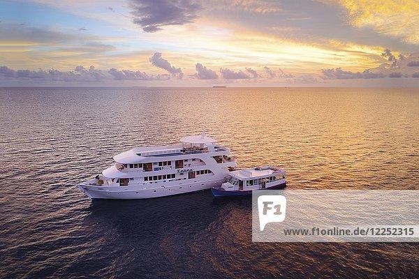 Tauchsafari-Schiff MS Keana mit Tauchdhoni ankert im Sonnenuntergang  Ari-Atoll  Indischer Ozean  Malediven  Asien