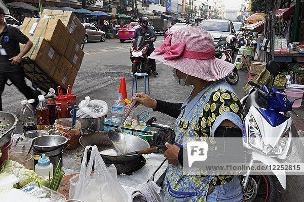 Cookshop  woman cooking at a streetfood stand  Yaowarat Road  Chinatown  Samphanthawong  Bangkok  Thailand  Asia