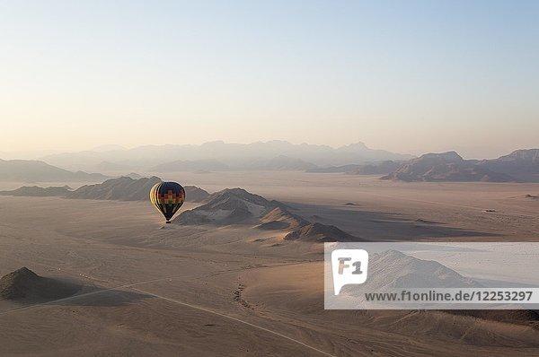 Heißluftballon über einer trockenen Ebene und einsamen Bergrücken  bei Tagesanbruch  Namib-Wüste  Luftaufnahme  NamibRand Nature Reserve  Namibia  Afrika