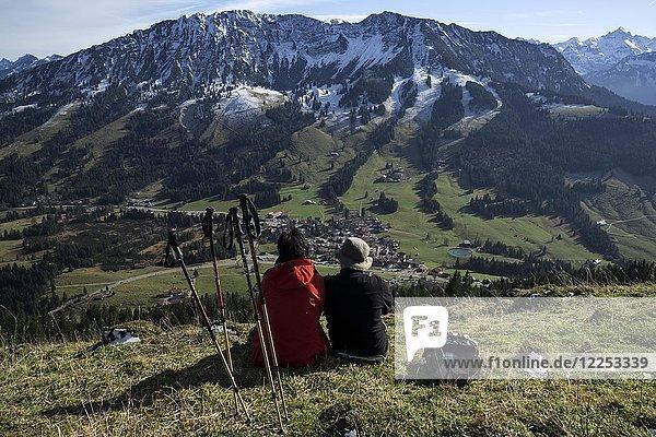 Zwei Wanderer sitzen im Gras und genießen den Ausblick auf Oberjoch und den Iseler  Oberjoch  Allgäu  Bayern  Deutschland  Europa