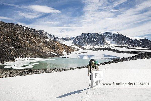 Mann beim Trekking im Schnee  Berglandschaft mit See  Westgrönland  Grönland  Nordamerika
