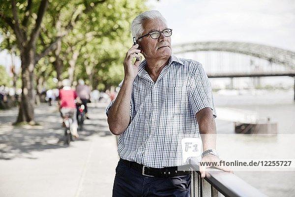 Grauhaariger Senior telefoniert mit seinem Smartphone auf der Kölner Rheinufer Promenade vor der Hohenzollernbrücke  Köln  Nordrhein-Westfalen  Deutschland  Europa