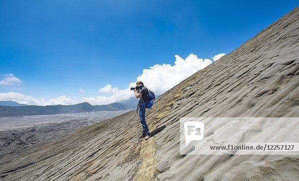 Schmaler Pfad am Kraterrand  junger Mann fotografiert  Krater des Vulkan Gunung Bromo  Nationalpark Bromo-Tengger-Semeru  Java  Indonesien  Asien