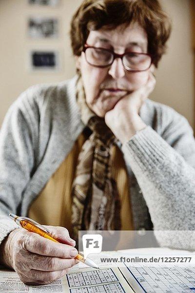 Seniorin sitzt zu Hause am Tisch und löst Rätsel  Sudoku  Kreuzworträtsel  Köln  Nordrhein-Westfalen  Deutschland  Europa