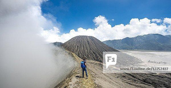 Junger Mann auf schmalem Pfad am Kraterrand  rauchender Vulkan Vulkan Gunung Bromo  Nationalpark Bromo-Tengger-Semeru  Java  Indonesien  Asien Junger Mann auf schmalem Pfad am Kraterrand, rauchender Vulkan Vulkan Gunung Bromo, Nationalpark Bromo-Tengger-Semeru, Java, Indonesien, Asien