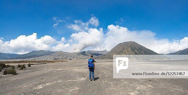 Young man in the caldera on his way to the crater of the Gnung Bromo  smoking volcano Gunung Bromo  Mt. Batok  Mt. Kursi  Mt. Gunung Semeru  Tengger Caldera  National Park Bromo-Tengger-Semeru  Java  Indonesia.