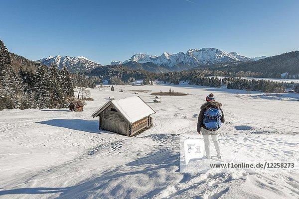 Frau steht in schneebedeckter Landschaft  zugefrorener Geroldsee im Winter  kleine Heustadel  Mittenwald  Karwendel  Oberbayern  Bayern  Deutschland  Europa