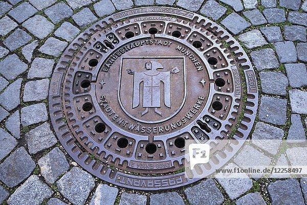Kanaldeckel mit Münchner Kindl  Landeshauptstadt München  Oberbayern  Bayern  Deutschland  Europa
