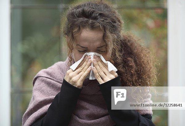 Symbolbild Erkältung  Grippe  Krankheit  Portrait einer Frau beim Nase putzen mit Papiertaschentuch