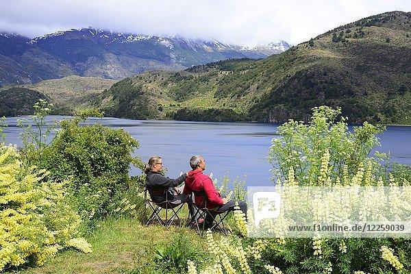 Couple on camping chairs at Lago Tranquilo  Valle Exploradores  near Puerto Rio Tranquilo  Región de Aysén  Chile  South America