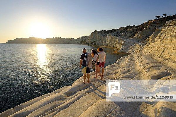 Tourists during sunset  rocky coast of Scala dei Turchi  limestone rocks  Realmonte  Province of Agrigento  Sicily  Italy  Europe
