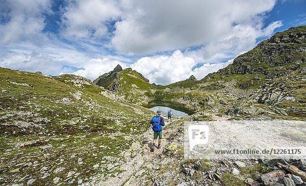 Wanderer und Wanderin an einem kleinen See im Klafferkessel  Schladminger Höhenweg  Schladminger Tauern  Schladming  Steiermark  Österreich  Europa