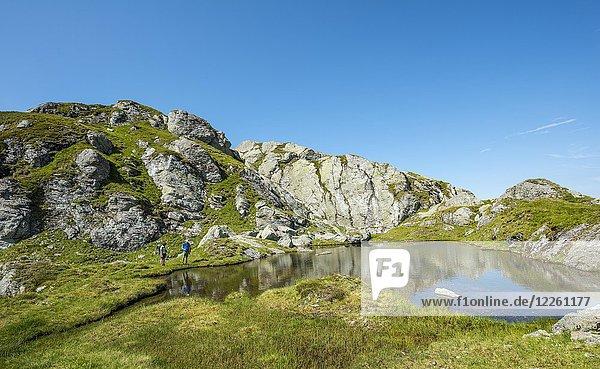 Zwei Wanderer an einem kleinen See  Schladminger Höhenweg  Schladminger Tauern  Schladming  Steiermark  Österreich  Europa Zwei Wanderer an einem kleinen See, Schladminger Höhenweg, Schladminger Tauern, Schladming, Steiermark, Österreich, Europa