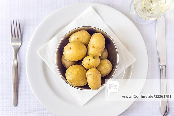 Cooked baby potatoes in silver bowl with cutlery and white wine  laid table