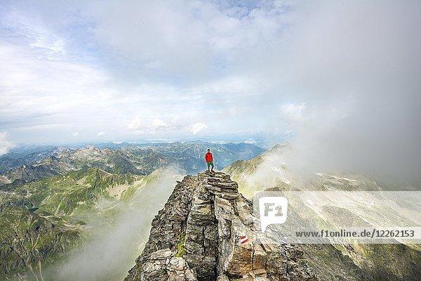 Wanderer auf dem Gipfel des Hochgolling mit aufziehenden Nebelschwaden  Schladminger Höhenweg  Schladminger Tauern  Schladming  Steiermark  Österreich  Europa Wanderer auf dem Gipfel des Hochgolling mit aufziehenden Nebelschwaden, Schladminger Höhenweg, Schladminger Tauern, Schladming, Steiermark, Österreich, Europa