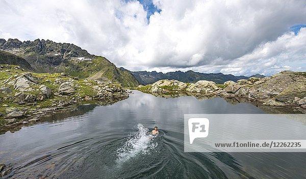 Junger Mann schwimmt in einem kleinen See  Klafferkessel  Schladminger Höhenweg  Schladminger Tauern  Schladming  Steiermark  Österreich  Europa Junger Mann schwimmt in einem kleinen See, Klafferkessel, Schladminger Höhenweg, Schladminger Tauern, Schladming, Steiermark, Österreich, Europa