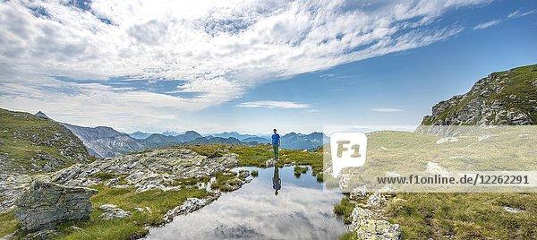 Wanderer spiegelt sich in einem kleinen See  Schladminger Höhenweg  Schladminger Tauern  Schladming  Steiermark  Österreich  Europa