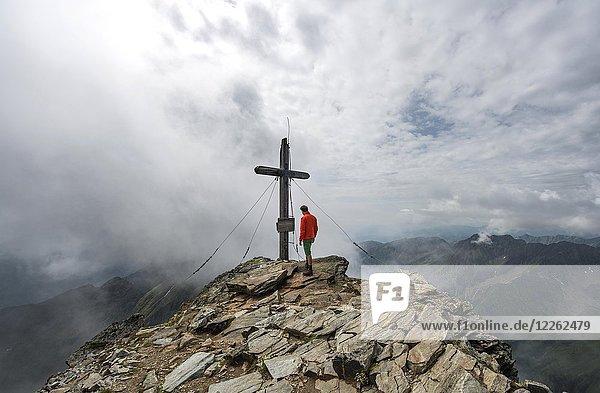 Wanderer am Gipfelkreuz des Hochgolling  Schladminger Höhenweg  Schladminger Tauern  Schladming  Steiermark  Österreich  Europa Wanderer am Gipfelkreuz des Hochgolling, Schladminger Höhenweg, Schladminger Tauern, Schladming, Steiermark, Österreich, Europa