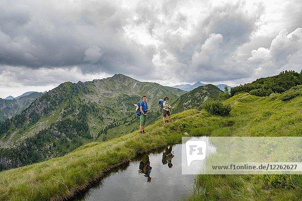 Wanderer und Wanderin spiegeln sich in einem kleinen See  Schladminger Höhenweg  Schladminger Tauern  Schladming  Steiermark  Österreich  Europa
