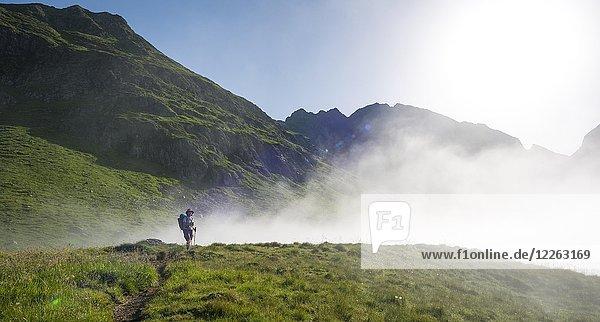 Wanderin auf dem Schladminger Höhenweg mit aufziehenden Nebelwolken  Schladminger Tauern  Schladming  Steiermark  Österreich  Europa
