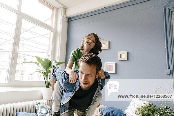 Glücklicher Vater trägt seinen Sohn huckepack zu Hause.