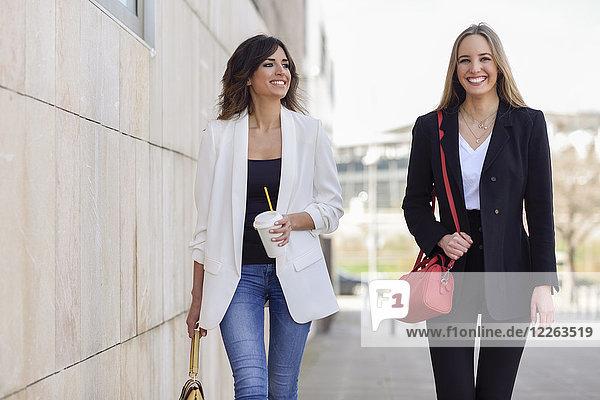Portrait von zwei glücklichen Geschäftsfrauen mit Handtaschen und Kaffee zum Spazierengehen auf dem Bürgersteig