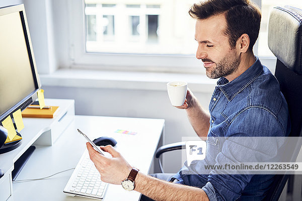 Smiling man looking at cell phone and drinking coffee at desk in office