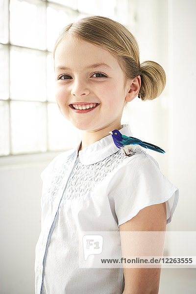 Portrait of happy little girl with toy bird on shoulder
