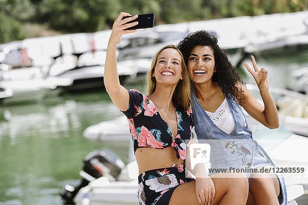 Zwei glückliche junge Frauen  die im Sommer einen Selfie am Yachthafen machen.
