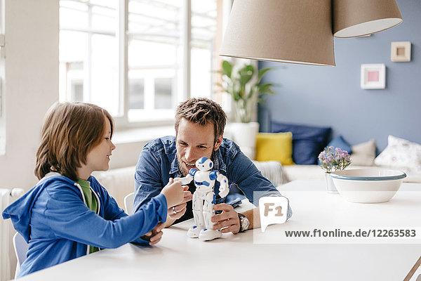 Glücklicher Vater und Sohn beim Spielen mit dem Roboter auf dem Tisch zu Hause
