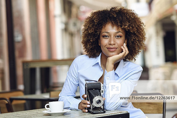 Portrait of smiling woman with vintage camera sitting in outdoor cafe