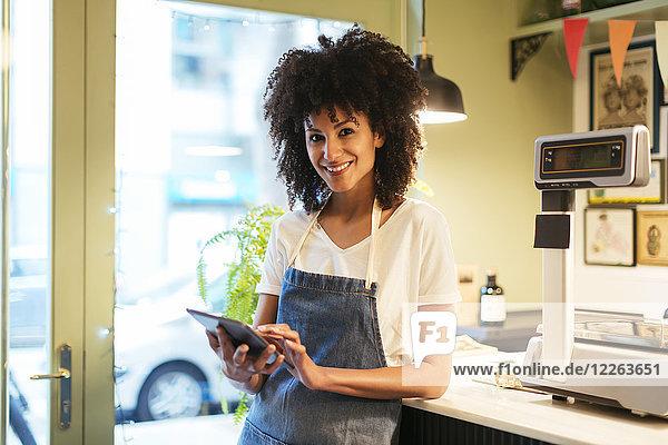 Porträt einer lächelnden Frau mit Tablette im Laden