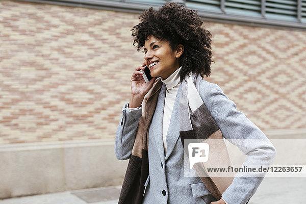 Spanien  Barcelona  lächelnde Frau am Handy in der Stadt